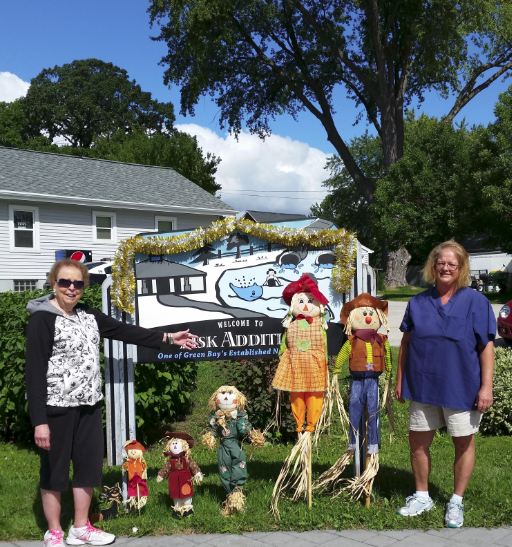 Women displaying sign and scarecrow dolls